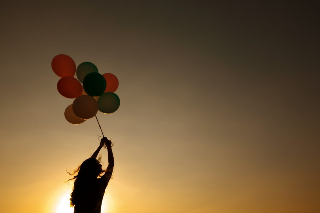 silhouette of young woman with flying balloons against the sky. happiness and dreams concept